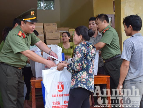 Thiếu tá Lưu Hồng Quân - Phó Tổng Biên tập Báo ANTĐ trao phần quà của Công ty TNHH Tuyết Nga đến người dân vùng lũ