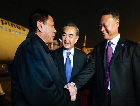 Tổng thống Philippines (bên trái) được Đại sứ Trung Quốc tại Philippines và Bộ trưởng Ngoại giao Trung Quốc đón ở sân bay Bắc Kinh hôm 18-10