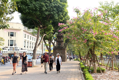 Du khách nước ngoài thong dong dạo bộ bên hồ Gươm Ảnh: LAM THANH
