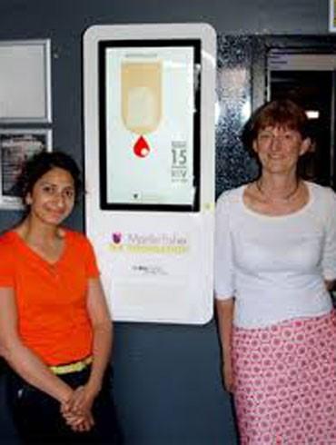 TS. Gill Dean (phải), chuyên gia về HIV của Tổ chức MFF bên mô hình chiếc máy xét nghiệm HIV tự động