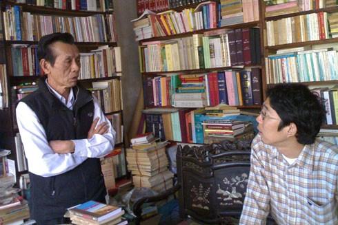Ông Phan Trác Cảnh (bên trái) trong kho sách của gia đình