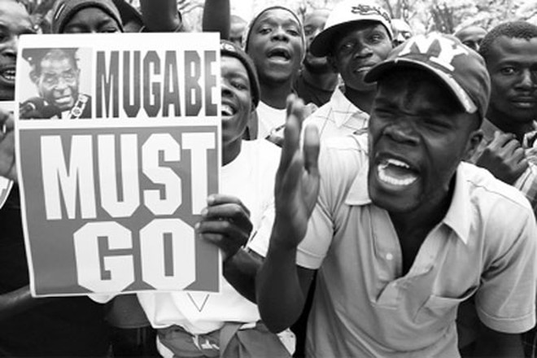 """Người biểu tình tập trung bên ngoài trụ sở Quốc hội Zimbabwe ở Thủ đô Harare cùng tấm biển ghi: """"Mugabe phải ra đi"""""""