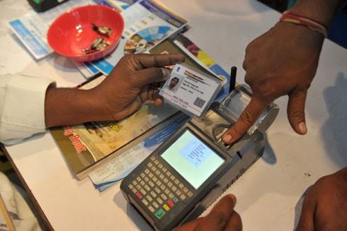 Một khách hàng Ấn Độ rút tiền gửi từ tài khoản ngân hàng bằng thẻ Aadhaar ở Hyderabad