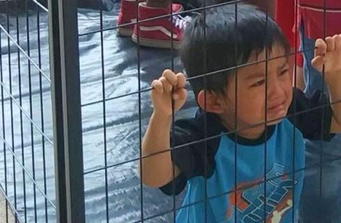 Một em bé bị tách khỏi cha mẹ nhập cư bất hợp pháp của mình trong những lồng sắt lớn