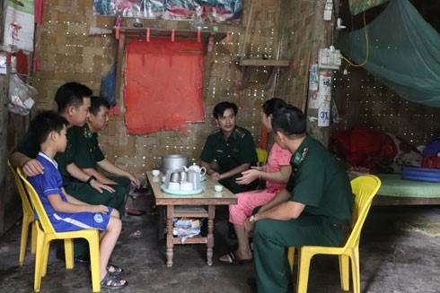 Cán bộ, chiến sĩ Đồn Biên phòng Bát Xát, BĐBP Lào Cai trao đổi với gia đình chị Thào Thị Liên (bản Qua, xã Bản Qua, huyện Bát Xát) về các thủ tục nhận nuôi cháu Thào Duy Dũng 11 tuổi mồ côi bố