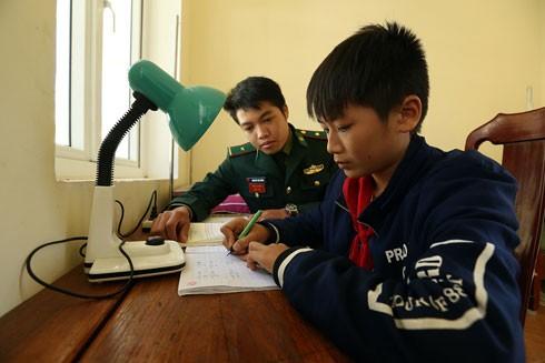 Chiến sỹ bộ đội biên phòng Điện Biên hướng dẫn kèm cặp con nuôi của đồn học bài tại đơn vị