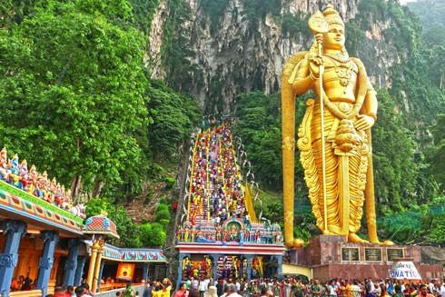 Tượng thần Murugan vàng rực cao 43m, từ đó leo lên cửa hang phải qua 300 bậc thang dốc đứng để vào động Batu