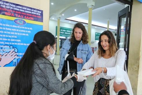 Phát khẩu trang tại cổng bệnh viện, cho du khách nước ngoài