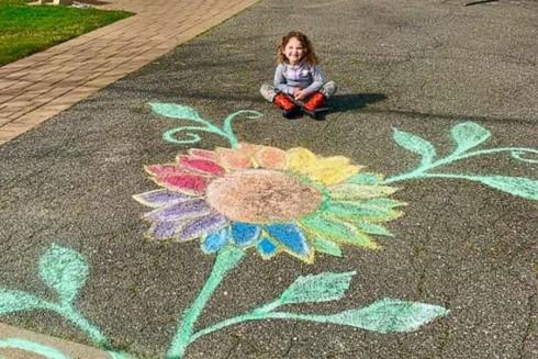 Bé Violet, 4 tuổi, ở Long Island, với bông hoa cầu vồng trước sân nhà để lan truyền hy vọng giữa cuộc khủng hoảng Covid-19