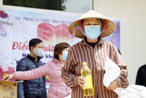 Niềm vui hiện lên trong ánh mắt người dân nghèo khi nhận lương thực tại các điểm phát gạo ở Hà Nội - Ảnh: LAM THANH