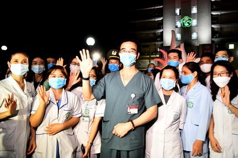 """Hình ảnh những y, bác sĩ của Bệnh viện Bạch Mai rạng rỡ trong đêm 12-4 với những tiếng hô """"Bạch Mai chiến thắng"""" vang lên vào thời khắc dỡ bỏ lệnh phong tỏa cách ly y tế khiến bất kỳ ai cũng xúc động Ảnh: LAM THANH"""