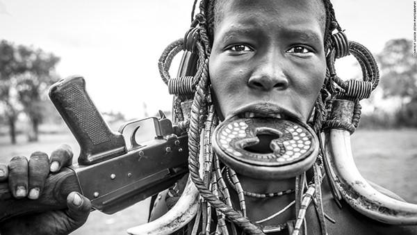 Một người phụ nữ của bộ lạc Mursi với khẩu súng trường AK-47. Trong con mắt của người Mursi, gia súc là tín hiệu đầu tiên của sự giàu có, nên với khẩu AK-47 này, họ sẽ bảo vệ tài sản của mình khỏi những kẻ cướp gia súc.