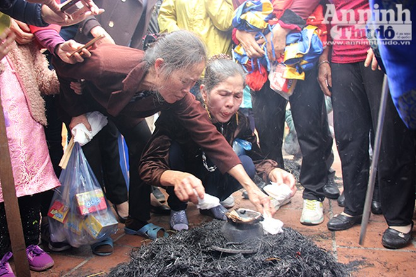 Các thành viên trong đội đang dùng giấy kiểm tra độ chín của gạo, khi nước bắt đầu cạn cũng là lúc các niêu cơm được vùi xuống để chín bằng sức nóng của tro rơm.