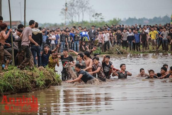 """Chen lấn, xô đẩy khiến cả người và phết đều xuống nước. Tuy nhiên cuộc """"thủy chiến""""cướp phết cũng không kém trên bãi đất."""