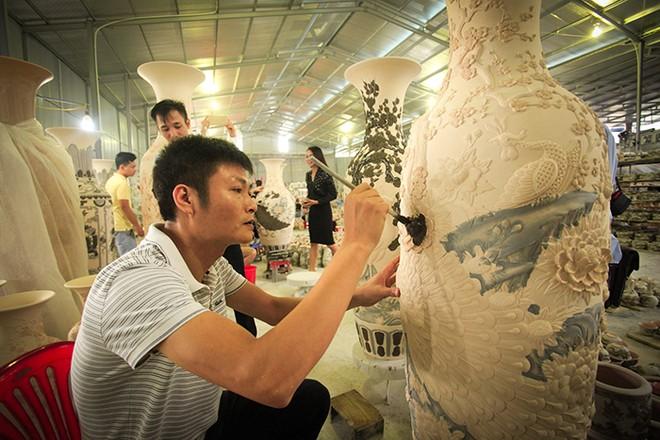 Các nghệ nhân chế tác thủ công mỹ nghệ Gia Tộc Việt say sưa với những nét hoa văn trên gốm