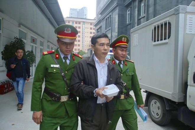 Cảnh sát hỗ trợ tư pháp dẫn giải bị cáo vào phòng xét xử