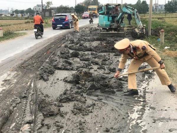 Lực lượng CSGT dùng xẻng và xe cẩu để dọn số lượng lớn bùn đất đổ trên đường