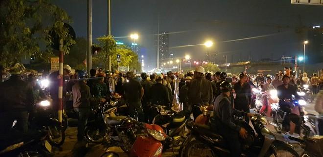 Rất đông người dân vây quanh chiếc xe ôtô