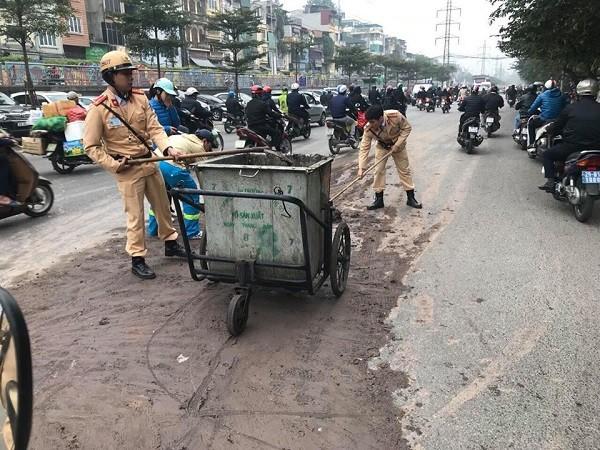 CSGT cùng nhân viên vệ sinh môi trường dọn sạch số bùn đất rơi vãi trên đường