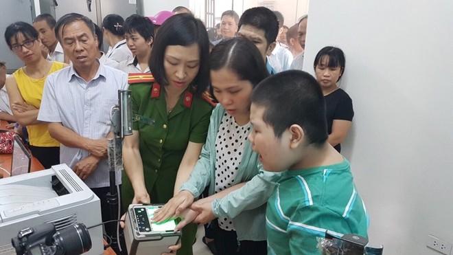 Thiếu tá Nguyễn Thanh Huyền và người thân giúp đỡ một em học sinh làm căn cước công dân