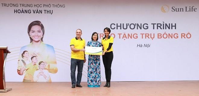 Đại diện Sun Life Việt Nam và Hoa hậu H'Hen Niê trao quà cho các trường học