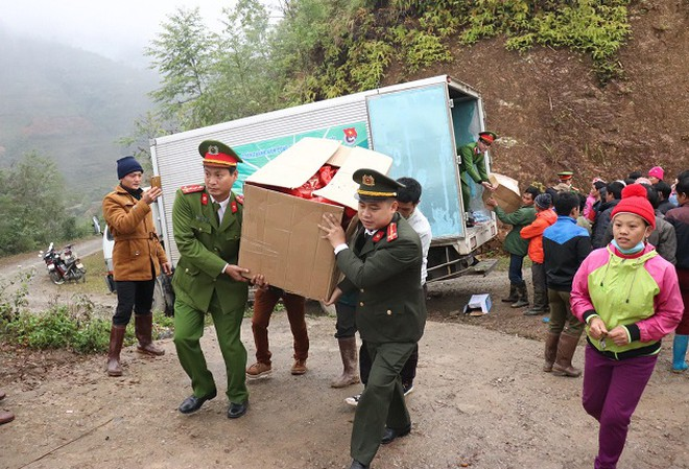 Cán bộ chiến sỹ Công an Hà Nội cùng người dân vận chuyển hàng hóa vào trường học ở xã Hưng Đạo