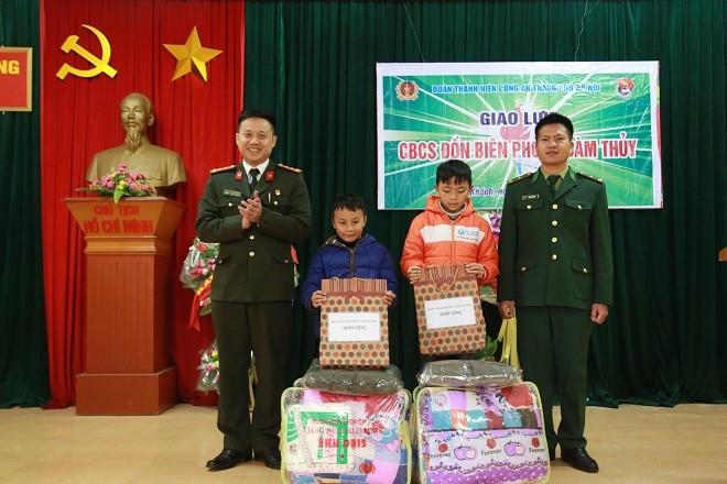 Đại úy Bùi Mạnh Hùng và Thiếu tá Bùi Văn Cường tặng quà cho các em nhỏ đang được Đồn Biên phòng Đàm Thủy nhận đỡ đầu