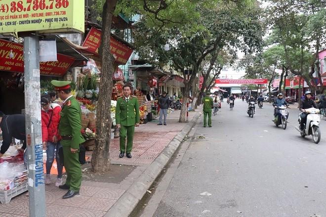 Các CBCS Công an quận Long Biên nhắc nhở người dân bày bán hàng hóa không lấn chiếm lòng đường, vỉa hè