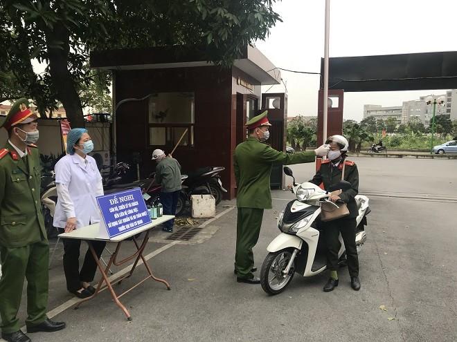 Cán bộ chiến sỹ được kiểm tra thân nhiệt khi ra vào cổng Công an quận Long Biên