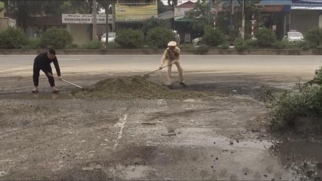 Hình ảnh lực lượng CSGT san lấp hố nước tại ngã ba đường