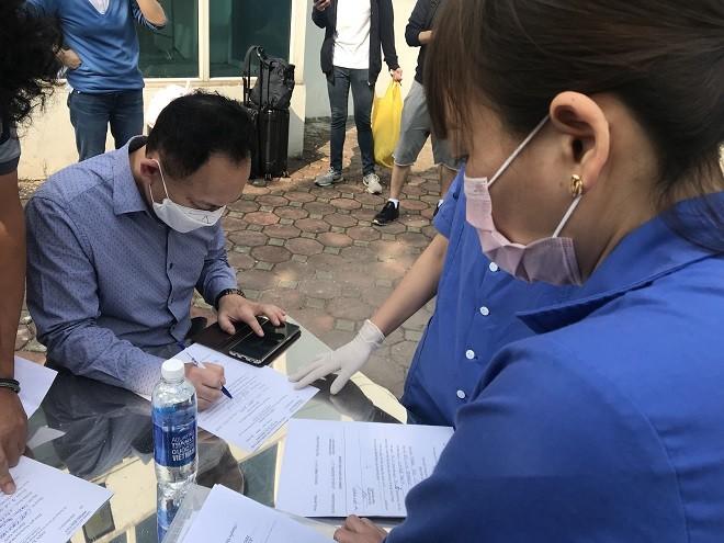 Nhân viên y tế hướng dẫn công dân làm thủ tục cần thiết sau khi hoàn thành cách ly