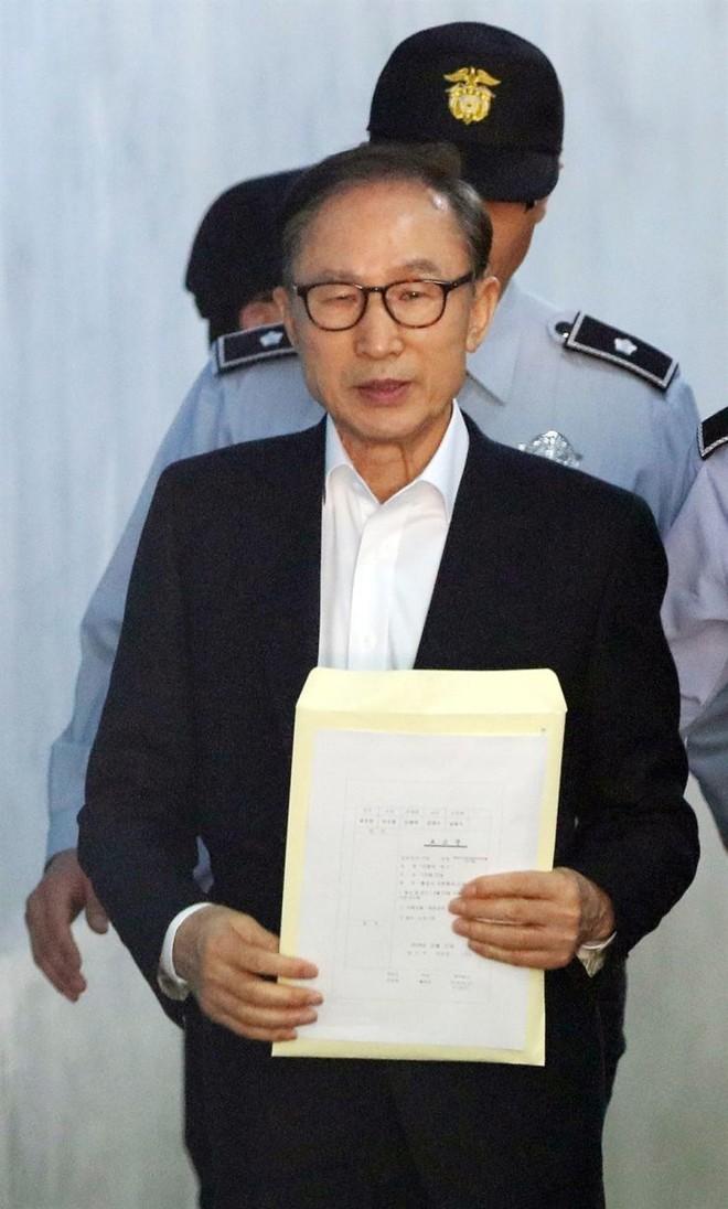 Nhân viên an ninh hộ tống ông Lee Myung-bak đến toà