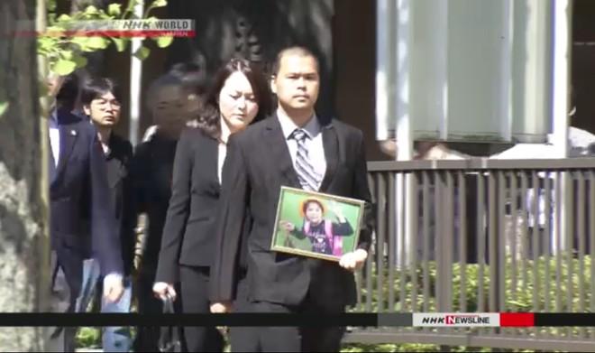 Anh Lê Anh Hào mang di ảnh của con tới dự phiên toà