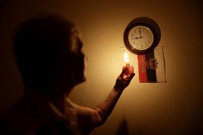 Một người phụ nữ dùng nến để xem đồng hồ khi bị mất điện ở thành phố Simferopil của Crimean vào ngày 26-12-2014