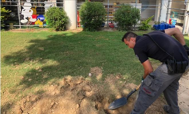Một cảnh sát đào những mảnh vỡ từ một quả rocket bắn vào sân trường mẫu giáo ngày 20-6-2018