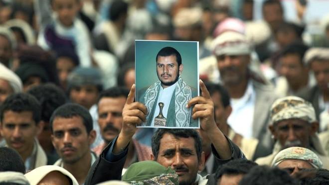 Người dân giơ cao bức ảnh chụp thủ lĩnh phiến quân Houthi ở Yemen Abdel Malek al-Huthi