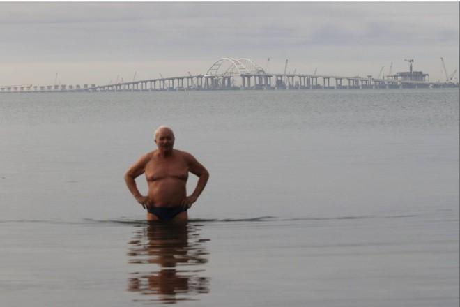 Một người đàn ông tắm tại eo biển Kerch, Crimea. Phía đằng sau là toàn cảnh cây cầu