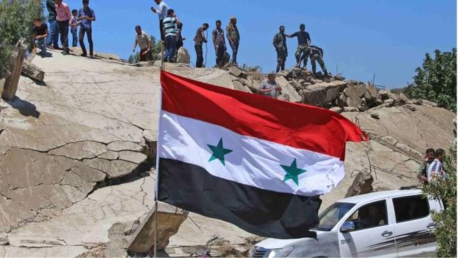 Lực lượng nổi dậy ở Syria đứng trên một đổng nát của một toà nhà