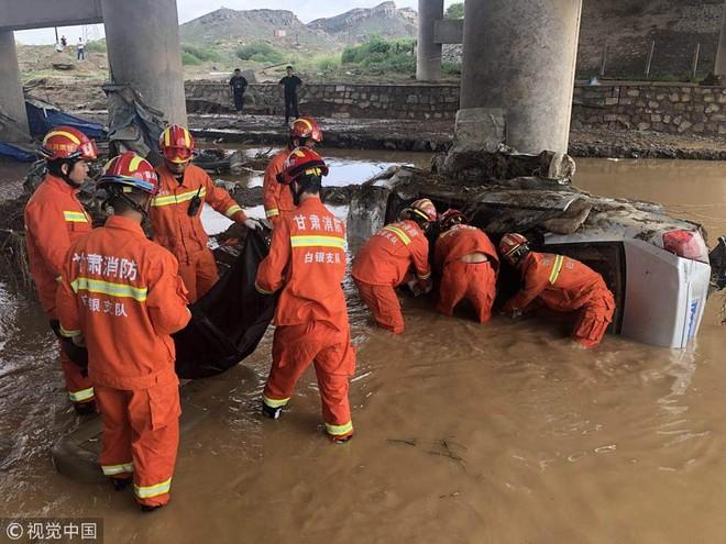 Lực lượng cứu hộ tìm kiếm nạn nhân trong chiếc xe chìm trong nước lụt