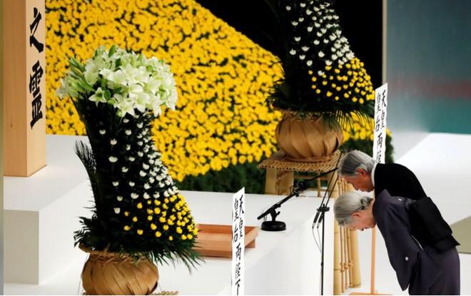 Nhật hoàng Akihito và Hoàng hậu Michiko cúi chào trước một bàn thờ trong khoảnh khắc tưởng niệm những người thiệt mạng trong Thế chiến thứ hai tại Budokan Hall, Tokyo ngày 15-8-2018