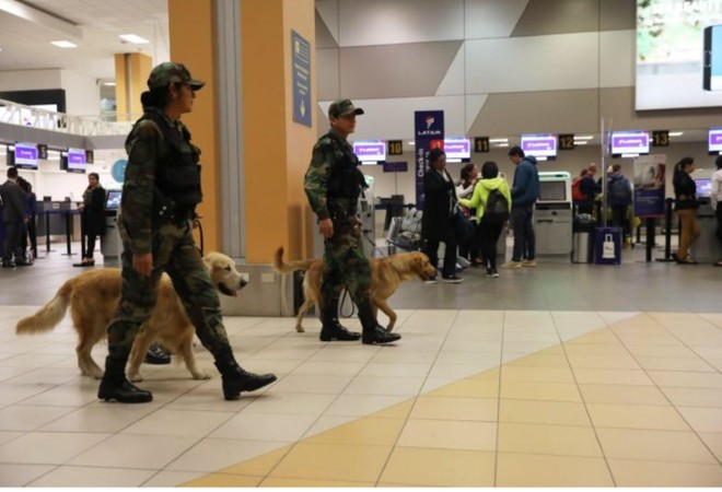 Cảnh sát tuần tra với chó nghiệp vụ gần cửa hàng của hãng hàng không LATAM ở sân bay Jorge Chavez, Callao, Peru, ngày 16-8-2018