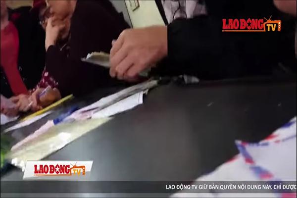 Phật tử nộp tiền để được tham dự lễ giải nghiệp (Ảnh: cắt từ clip Lao Động)