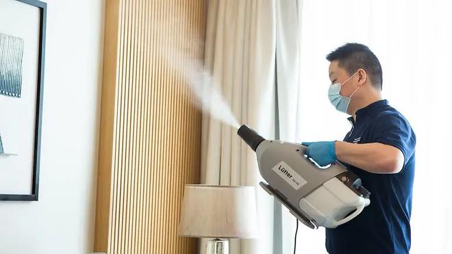 Nhân viên tại khách sạn xịt khử trùng vệ sinh phòng