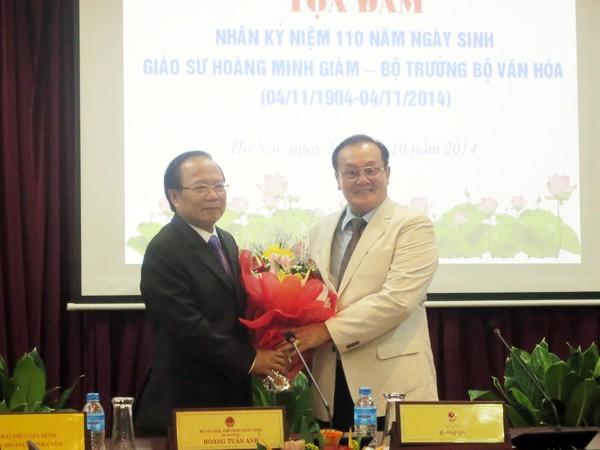 Bộ trưởng Bộ VH-TT&DL Hoàng Tuấn Anh tặng hoa ông Hoàng Vĩnh Giang - con trai cố GS Hoàng Minh Giám