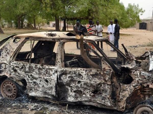 Một chiếc ô tô cháy đen và đầy vết đạn sau khi một nhóm Boko Haram đi qua
