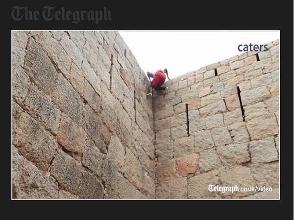 Raju đang dùng tay không leo lên đỉnh bức tường đá