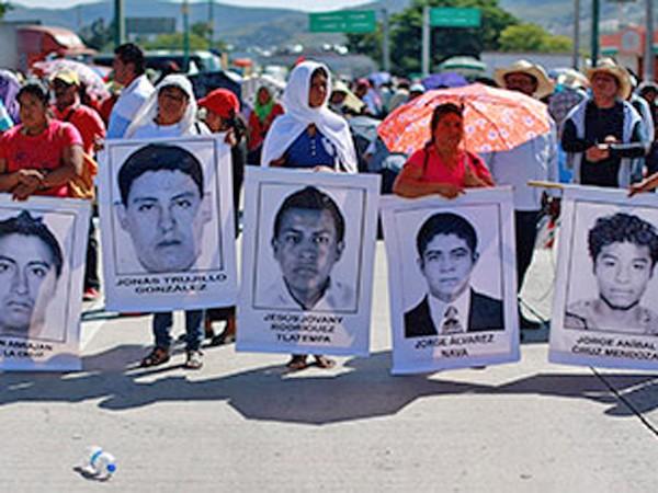 Người biểu tình mang theo ảnh của các nạn nhân vụ thảm sát ngày 26-9, tiếp tục đòi công lý