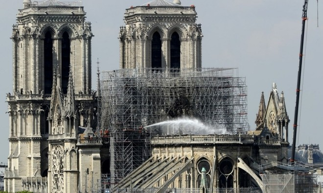Lính cứu hỏa phun nước dập tắt ngọn lửa trong vụ cháy Nhà thờ Đức bà Paris tháng 4