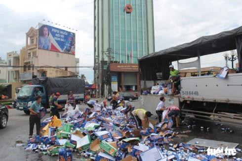 Nhiều người dân đã giúp tài xế gom lại số bia đổ xuống đường (Ảnh: Hoài Thương)