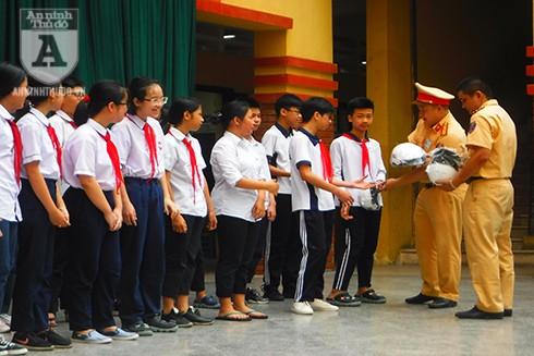 Cán bộ, chiến sĩ trao tặng mũ bảo hiểm cho các em học sinh